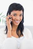 Σαγηνευτική μαύρη μαλλιαρή γυναίκα στα άσπρα ενδύματα που καλούν κάποιο με το κινητό τηλέφωνό της Στοκ φωτογραφίες με δικαίωμα ελεύθερης χρήσης