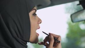 Σαγηνευτική μουσουλμανική κυρία που εφαρμόζει το κόκκινο κραγιόν στο αυτοκίνητο, φεμινισμός, κοκέτα απόθεμα βίντεο