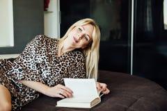 Σαγηνευτική νέα ξανθή γυναίκα με το βιβλίο στο κρεβάτι στην κρεβατοκάμαρα στοκ φωτογραφίες