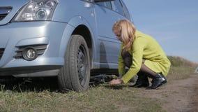 Σαγηνευτική ξανθή γυναίκα που δοκιμάζει τη ρόδα αλλαγής σε ένα αυτοκίνητο στον αγροτικό δρόμο κίνηση αργή φιλμ μικρού μήκους