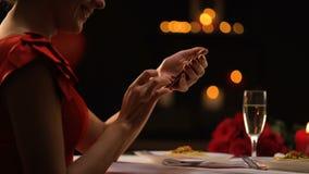 Σαγηνευτικό γυναικείο να τυλίξει smartphone app στο εστιατόριο, περιμένοντας άτομο, ραντεβού στα τυφλά φιλμ μικρού μήκους