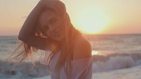 Σαγηνευτικό κορίτσι με τη μακρυμάλλη τοποθέτηση στο ηλιοβασίλεμα επάνω απόθεμα βίντεο