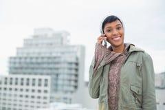 Σαγηνευτικό νέο πρότυπο στα χειμερινά ενδύματα που καλούν κάποιο με το κινητό τηλέφωνό της Στοκ Φωτογραφίες