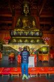 ΣΑΓΚΆΗ, ΚΙΝΑ: Θρησκευτικός βωμός με το μεγάλο χρυσό άγαλμα του Βούδα που κεντροθετείται ανωτέρω, τοποθετημένο εσωτερικό Jing ` μι Στοκ εικόνα με δικαίωμα ελεύθερης χρήσης