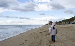 Σακάκι ένδυσης μικρών κοριτσιών και περίπατος μαντίλι στην παραλία άμμου medite πλησίον Στοκ εικόνες με δικαίωμα ελεύθερης χρήσης