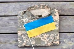 Σακάκι κάλυψης και ουκρανική σημαία στο ξύλο Στοκ φωτογραφία με δικαίωμα ελεύθερης χρήσης