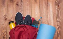 Σακίδιο πλάτης με τον αθλητικό εξοπλισμό στο ξύλινο πάτωμα Στοκ Εικόνα