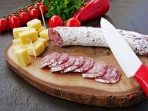 Σαλάμι λουκάνικων που τεμαχίζονται και κύβοι τυριών Στοκ εικόνα με δικαίωμα ελεύθερης χρήσης