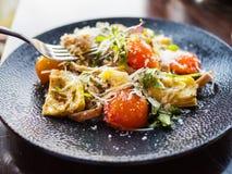 Σαλάτα αγκιναρών και ντοματών με το τυρί στο σκοτεινό πιάτο πέρα από ένα ξύλο στοκ φωτογραφία