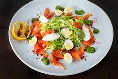 Σαλάτα από τα αυγά, τα πράσινα και την πέστροφα λευκό πιάτων στοκ εικόνες
