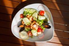 Σαλάτα θαλασσινών με τα λαχανικά σε ένα άσπρο πιάτο σε έναν ξύλινο πίνακα Στοκ φωτογραφία με δικαίωμα ελεύθερης χρήσης