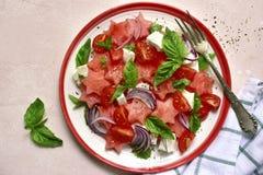 Σαλάτα καρπουζιών με την ντομάτα, το τυρί φέτας, το κόκκινους κρεμμύδι και το βασιλικό Τοπ άποψη με το διάστημα αντιγράφων στοκ εικόνα