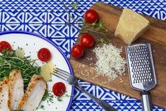 Σαλάτα με τη σαλάτα Caesar κοτόπουλου με τα μικροϋπολογιστής-πράσινα, τις ντομάτες κερασιών και την παρμεζάνα σε ένα μπλε υπόβαθρ στοκ φωτογραφία