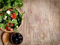 Σαλάτα με τις ντομάτες και τις ελιές στο ξύλινο υπόβαθρο Στοκ φωτογραφία με δικαίωμα ελεύθερης χρήσης