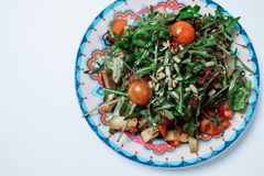 Σαλάτα με τις ντομάτες σαλάτας και κερασιών πυραύλων σε ένα άσπρο backgroun Στοκ Εικόνες