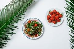 Σαλάτα με τις ντομάτες σαλάτας και κερασιών πυραύλων σε ένα άσπρο backgroun Στοκ Φωτογραφία