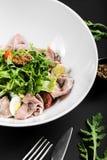 Σαλάτα με το βόειο κρέας ψητού, το arugula, τις ντομάτες κερασιών, το αυγό και τη μουστάρδα σιταριού σε ένα μαύρο υπόβαθρο κλείστ Στοκ Εικόνες