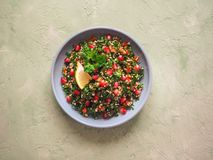 Σαλάτα με το κουσκούς και πράσινα χορτάρια σε ένα πιάτο στον πίνακα στοκ φωτογραφία με δικαίωμα ελεύθερης χρήσης