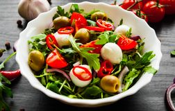 Σαλάτα με το πράσινο rucola, τυρί, ελιά, ντομάτα, κρεμμύδι, πιπέρι στο άσπρο κύπελλο στο σκοτεινό ξύλινο υπόβαθρο Στοκ φωτογραφίες με δικαίωμα ελεύθερης χρήσης