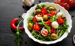 Σαλάτα με το πράσινο rucola, τυρί, ελιά, ντομάτα, κρεμμύδι, πιπέρι στο άσπρο κύπελλο στο σκοτεινό ξύλινο υπόβαθρο Στοκ Εικόνες