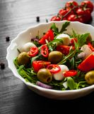 Σαλάτα με το πράσινο rucola, τυρί, ελιά, ντομάτα, κρεμμύδι, πιπέρι στο άσπρο κύπελλο στο σκοτεινό ξύλινο υπόβαθρο Στοκ εικόνες με δικαίωμα ελεύθερης χρήσης