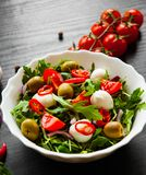 Σαλάτα με το πράσινο rucola, τυρί, ελιά, ντομάτα, κρεμμύδι, πιπέρι στο άσπρο κύπελλο στο σκοτεινό ξύλινο υπόβαθρο Στοκ φωτογραφία με δικαίωμα ελεύθερης χρήσης