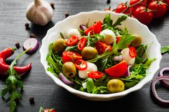 Σαλάτα με το πράσινο rucola, τυρί, ελιά, ντομάτα, κρεμμύδι, πιπέρι στο άσπρο κύπελλο στο σκοτεινό ξύλινο υπόβαθρο Στοκ εικόνα με δικαίωμα ελεύθερης χρήσης