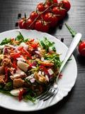 Σαλάτα με το πράσινο rucola, τυρί, τόνος, κρεμμύδι, πιπέρι στο άσπρο κύπελλο στο σκοτεινό ξύλινο υπόβαθρο Στοκ Φωτογραφίες