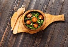 Σαλάτα με το arugula, τις ντομάτες και τα καρύδια πεύκων σε ένα ξύλινο κύπελλο Στοκ εικόνα με δικαίωμα ελεύθερης χρήσης