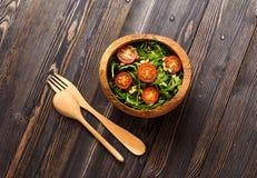 Σαλάτα με το arugula, τις ντομάτες και τα καρύδια πεύκων σε ένα ξύλινο κύπελλο Στοκ Εικόνα