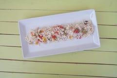 Σαλάτα ρυζιού σε έναν άσπρο δίσκο στο πράσινο ξύλο άνωθεν Στοκ Εικόνα