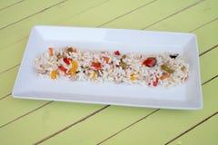 Σαλάτα ρυζιού σε έναν άσπρο δίσκο στο πράσινο ξύλο Στοκ εικόνα με δικαίωμα ελεύθερης χρήσης