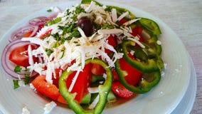 Σαλάτα σε ένα άσπρο πιάτο με το κρεμμύδι, τις ελιές και το ξυμένο τυρί στοκ φωτογραφία με δικαίωμα ελεύθερης χρήσης