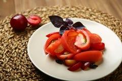 Σαλάτα της ντομάτας και των κόκκινων δαμάσκηνων με το βασιλικό για μια υγιεινή διατροφή Στοκ Εικόνες