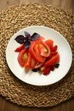 Σαλάτα της ντομάτας και των κόκκινων δαμάσκηνων με το βασιλικό για μια υγιεινή διατροφή Στοκ φωτογραφία με δικαίωμα ελεύθερης χρήσης