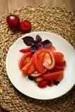 Σαλάτα της ντομάτας και των κόκκινων δαμάσκηνων με το βασιλικό για μια υγιεινή διατροφή Στοκ εικόνα με δικαίωμα ελεύθερης χρήσης