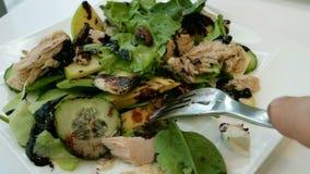 Σαλάτα τον τόνο, τα λαχανικά, το μαρούλι και το τυρί που αναμιγνύονται με με ένα δίκρανο φιλμ μικρού μήκους