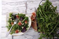 Σαλάτα φθινοπώρου του arugula, σύκα σε ένα άσπρο πιάτο πήλινου είδους Στοκ φωτογραφία με δικαίωμα ελεύθερης χρήσης