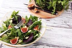 Σαλάτα φθινοπώρου του arugula, σύκα σε ένα άσπρο πιάτο πήλινου είδους Στοκ Εικόνα