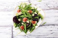 Σαλάτα φθινοπώρου του arugula, σύκα σε ένα άσπρο πιάτο πήλινου είδους Στοκ Φωτογραφία