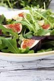 Σαλάτα φθινοπώρου του arugula, σύκα σε ένα άσπρο πιάτο πήλινου είδους Στοκ Εικόνες