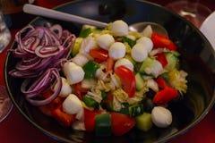 Σαλάτα φρέσκων λαχανικών με τις σφαίρες μοτσαρελών που διακοσμούνται με τα κόκκινα δαχτυλίδια κρεμμυδιών στοκ φωτογραφίες
