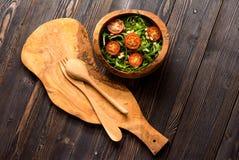 Σαλάτα Arugula με τις ντομάτες και τα καρύδια πεύκων σε ένα ξύλινο τόξο Στοκ φωτογραφίες με δικαίωμα ελεύθερης χρήσης