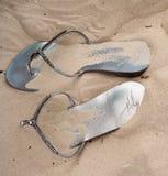 Σανδάλια πτώσης κτυπήματος που ξεχνιούνται στην άμμο Στοκ Εικόνες