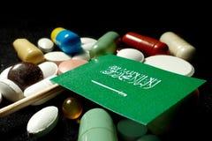 Σαουδαραβική σημαία με το μέρος των ιατρικών χαπιών που απομονώνεται στο μαύρο β Στοκ Εικόνες