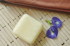 Σαπούνι και πετσέτα με το μπλε ιώδες λουλούδι μπιζελιών στο χαλί μπαμπού στοκ φωτογραφίες