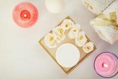 Σαπούνι υπό μορφή τριαντάφυλλων στο άσπρο υπόβαθρο Οι πετσέτες, κεριά, α μπορούν της κρέμας στοκ φωτογραφία