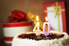 Σαράντα έτη γενεθλίων Κέικ με το κάψιμο των κεριών και των δώρων στοκ εικόνα