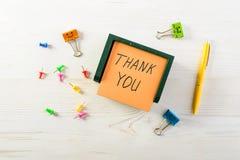 Σας ευχαριστούμε που γράφεστε στη μετα αυτοκόλλητη ετικέττα σημειώσεων με τη μάνδρα ελαφρύ σε ξύλινο Στοκ Φωτογραφία
