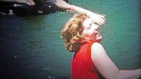 ΣΑΤΑΝΟΥΓΚΑ, ΗΠΑ - 1954: Οι γυναίκες που αγωνίζονται να πάνε προσχωρούν στην ομάδα στη λίμνη με έναν σωλήνα επιπλεόντων σωμάτων απόθεμα βίντεο